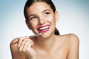 jeune femme tentante avec pinceau à lèvres