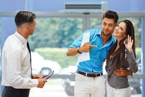 jeune couple célébrant l'achat de voiture photo