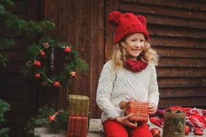 Fille enfant heureuse célébrant Noël en plein air à la maison de campagne photo