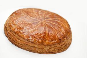 Une pâtisserie galette des rois dorée isolée sur blanc photo