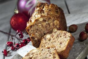 Gâteau aux fruits de Noël avec des noix et des décorations de Noël sur planche de bois