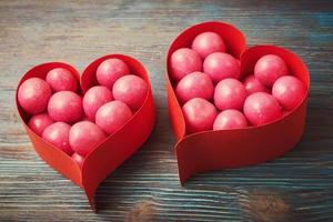 Bonbons sucrés dans des boîtes en forme de coeur sur fond de bois vintage photo