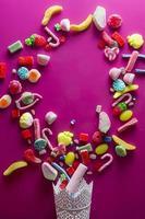 Bonbons colorés mélangés sur fond rose, vacances pour enfants photo