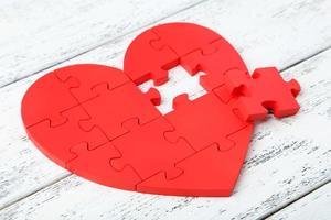 Coeur de puzzle rouge sur fond en bois blanc