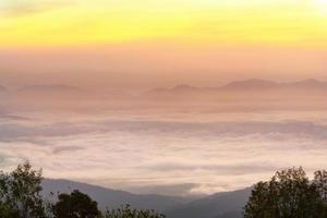montagnes dans un brouillard avec soleil et nuages