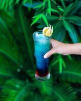 femme tenant un cocktail de couleur bleue