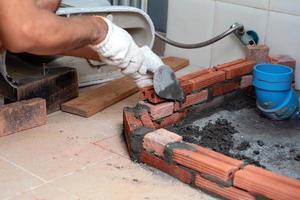 ouvrier du bâtiment pose des briques rouges