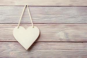 Coeur blanc suspendu sur fond vintage en bois clair photo