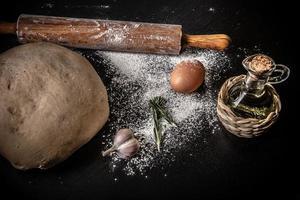 pâte à bord avec de la farine. huile d'olive, œufs, rouleau à pâtisserie