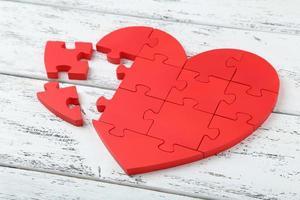 Coeur de puzzle rouge sur fond en bois blanc photo