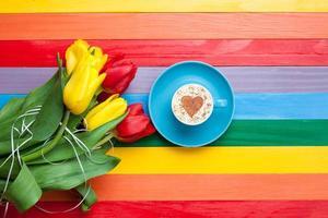 tasse de cappuccino en forme de coeur et bouquet de tulipes photo