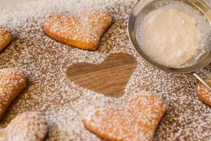 Poweder de biscuits en forme de coeur avec du sucre, une silhouette, passoire photo