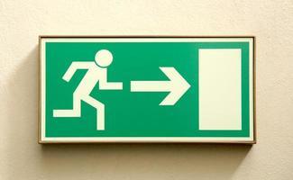 Panneau de sortie de secours de l'homme qui court vers une porte