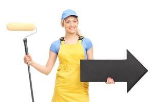 peintre femme tenant un rouleau à peinture et une flèche