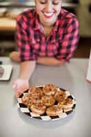 jeune femme, tenue, plaque, de, gâteaux fraîchement cuits, dans, boulangerie