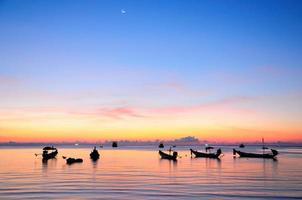 coucher de soleil doré sur une mer avec silhouette de navires photo