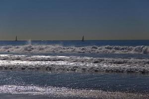 vagues et voiliers au coucher du soleil