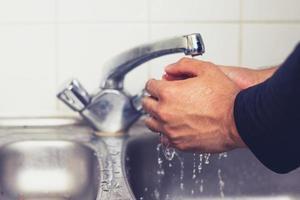 L'homme se lave les mains dans un évier de cuisine