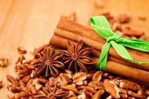 Bâtons de cannelle, anis et noix de pécan sur une table en bois photo