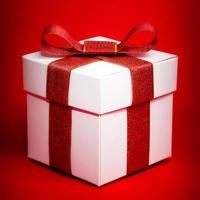 boîte blanche avec un ruban rouge sur fond rouge photo