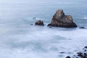 roches côtières de l'océan au soir avec des vagues floues