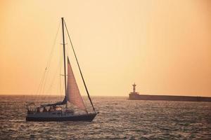 bateau à voile contre le coucher du soleil de la mer