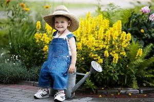 petit garçon avec arrosoir dans le parc d'été