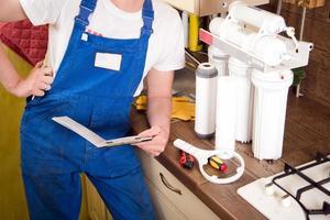 jeune beau plombier réparations de plomberie. filtre à eau de remplacement