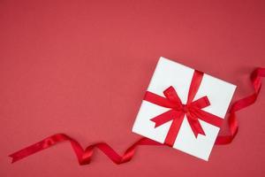 boîte cadeau wrap ruban de soie sur fond rouge photo