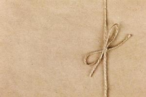 Ficelle ou ficelle attachée à un arc sur fond de papier kraft photo
