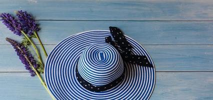 chapeau de femme sur fond bleu et fleurs