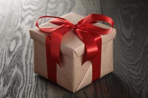 boîte-cadeau rustique avec noeud de ruban rouge photo