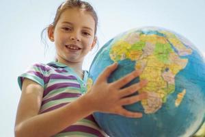 mignonne petite fille tenant un globe