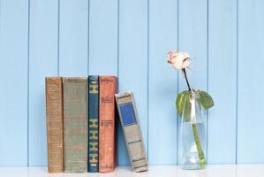 pile de livres et rose blanche dans la bouteille