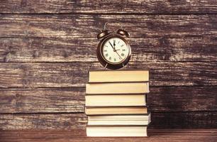 réveil et livres sur table en bois. photo