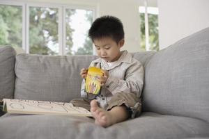 garçon avec livre de coloriage assis sur le canapé photo