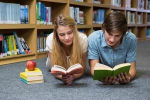 Étudiants lisant un livre allongé sur le sol de la bibliothèque photo