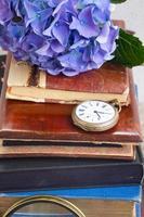 pile de vieux livres avec des fleurs et une horloge