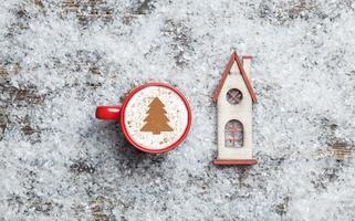 Cappuccino avec forme d'arbre de Noël et jouet maison sur artificielle