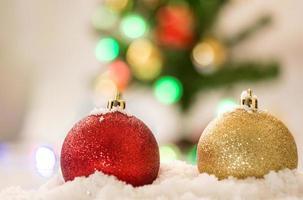 Boule de Noël rouge et or sur neige avec chrismas photo