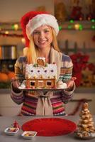 Happy teenage girl in santa hat montrant la maison de biscuits de Noël