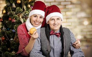 jeune couple en casquettes de père Noël.