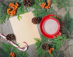 carte de Noël avec tasse de cacao, sapin, pommes de pin et rowan