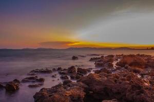 plage rocheuse au coucher du soleil photo