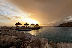 Coucher de soleil derrière des cabanes de paille dans la baie tropicale