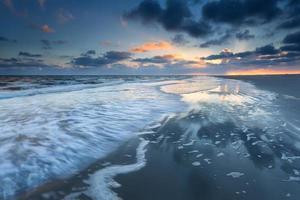 Lever du soleil sur la côte de la mer du Nord à marée basse photo