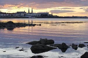 le soleil se couche derrière la ville portuaire.