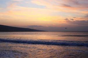 lever de soleil spectaculaire derrière les nuages au bord de la mer photo
