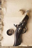 boussole et pistolet sur le vieux fond de papier photo