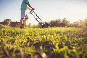 jeune homme tondre l'herbe